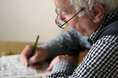Älterer Mann löst ein Kreuzworträtsel