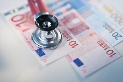 Stethoskop liegt auf Euro-Geldscheinen.