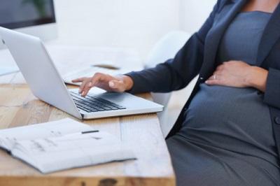 Schwangere Frau sitzt mit Laptop am Schreibtisch