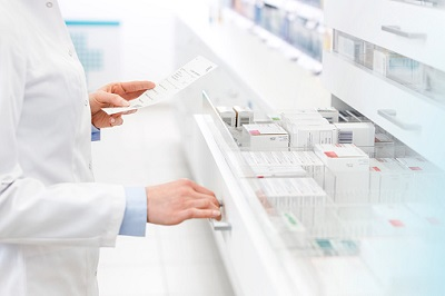 Apothekerin sucht mit Rezept in der Hand nach Medikament.