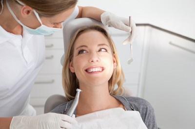 Eine Zahnärztin behandelt eine lächelnde Patientin.