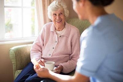 Seniorin spricht mit Krankenschwester.