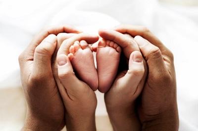 Hände von Vater, Mutter und Baby