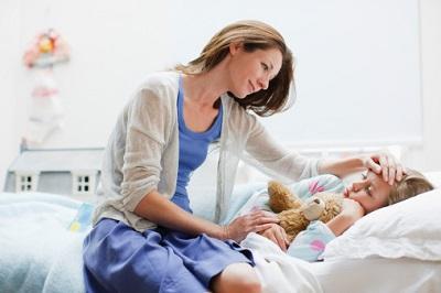 Eine Mutter pflegt ihr krankes Kind zu Hause.