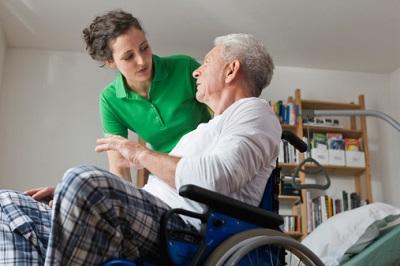 Frau betreut Senior im Rollstuhl.
