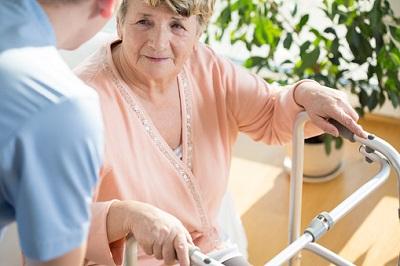 Pfleger kümmert sich um Seniorin mit Rollator.