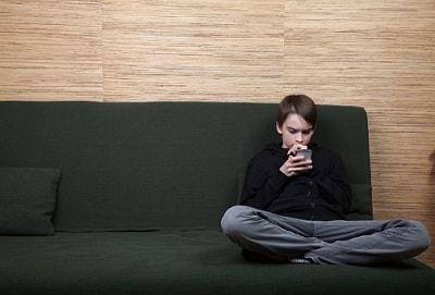 Ein Kind sitzen mit seinem Handy allein auf dem Sofa.