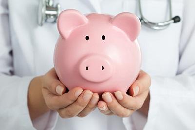 Eine Ärztin hält ein Sparschwein in der Hand.