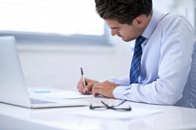 Angestellter arbeitet am Schreibtisch mit Laptop und Stift