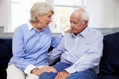 Älteres Ehepaar unterhält sich auf Sofa sitzend.