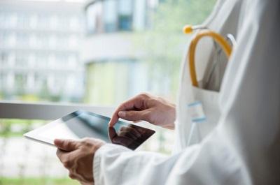 Arzt mit Stethoskop hält Tablet in der Hand