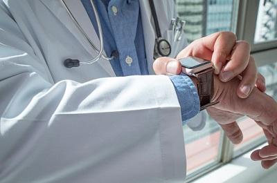 Arzt schaut auf seine Smartwatch - Ausschnitt