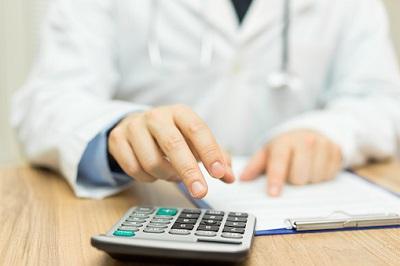 Ein Arzt tippt auf einem Taschenrechner.