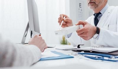 Arzt reicht Patient ein Medikamtent.