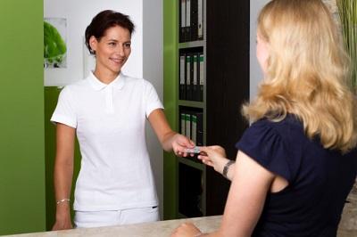 Sprechstundenhilfe überreicht Patientin die Gesundheitskarte