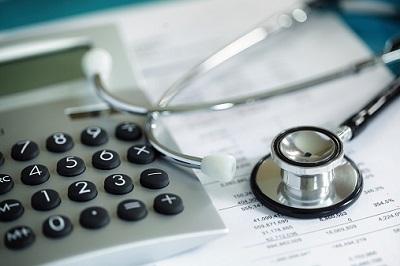 Taschenrechner und Stethoskop auf Rechnung