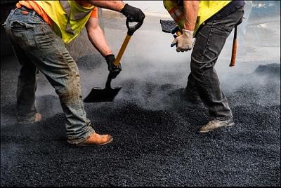 Straßenarbeiter in Warnwesten schaufeln Teer.
