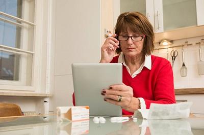 Ältere Frau mit Medikament, Beipackzettel und Tablet