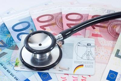 Stethoskop mit Geldscheinen und Versichertenkarte