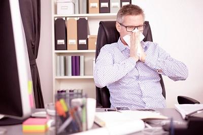 Arbeitnehmer schnäuzt sich im Büro in Taschentuch.