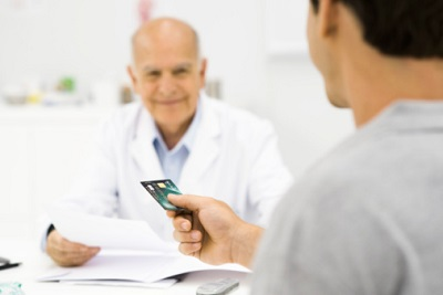 Ein Patient reicht seinem Arzt eine Kreditkarte.