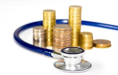 Ein Stethoskop umschlingt einen Stapel aus Münzen.