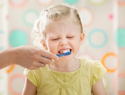 Mutter putzt kleiner Tochter die Zähne