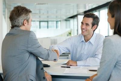 Versicherungsvertreter mit Kunden beim Vertragsabschluss
