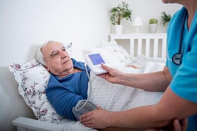 Älterer Mann mit Pflegerin im Pflegeheim