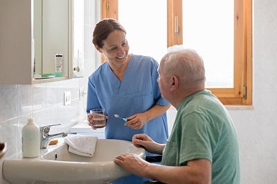 Altenpflegerin mit Senior im Badezimmer