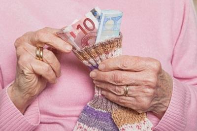 Seniorin entnimmt Geldscheine aus einem Sparstrumpf