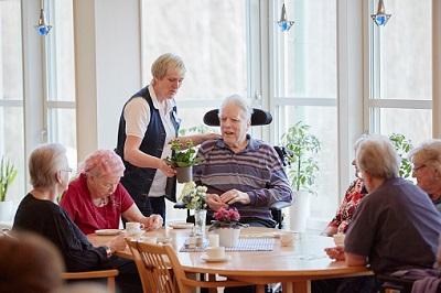 Bewohner eines Altenheims sitzen zusammen.