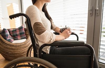 Jugendliche sitzt Zuhause im Rollstuhl.