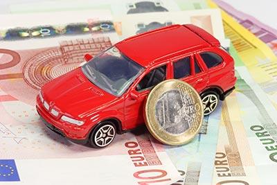 Spielzeugauto auf Geldscheinen mit Ein-Euro-Münze