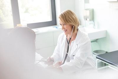 Ärztin misst Blutdruck bei einer Patientin