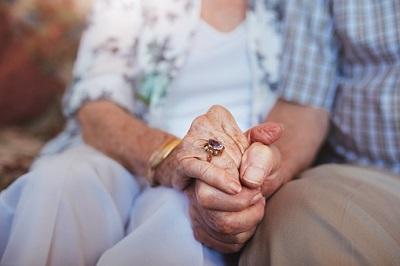 Älteres Paar hält sich an den Händen.