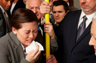 Niesende Geschäftsfrau in U-Bahn mit anderen Passagieren
