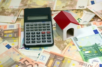 Kleines Haus und Taschenrechner auf Geldscheinen