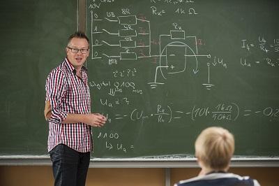 Lehrer steht vor Schulklasse an der Tafel