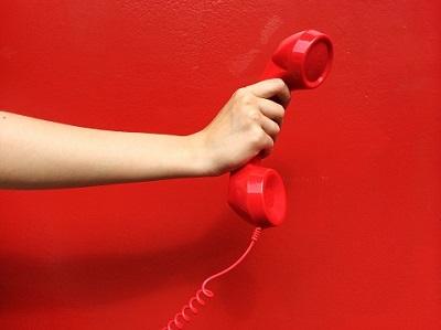Roter Telefonhörer vor roter Wand