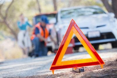 Warndreieck mit Mechniker und Autos im Hintergrund