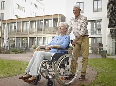 Älterer Mann schiebt Frau im Rollstuhl