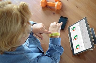 Ältere Frau mit Fitness-Tracker, Handy und Tablet