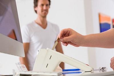 Frau steckt Gesundheitskarte in Kartenlesegerät.