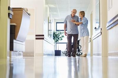 Krankenschwester hilft älterem Patienten auf dem Krankenhausflur.