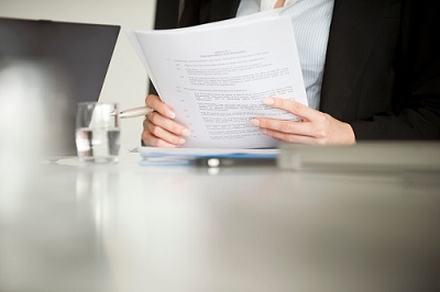 Business-Frau hält einen Vertrag in den Händen.