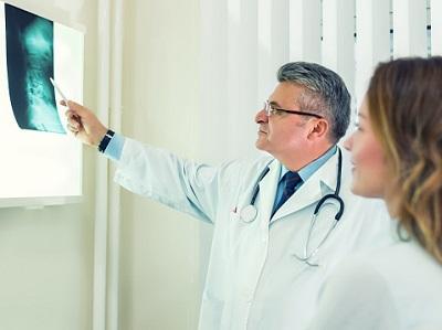 Arzt und Patientin schauen auf Röntgenaufnahme von Wirbelsäule.