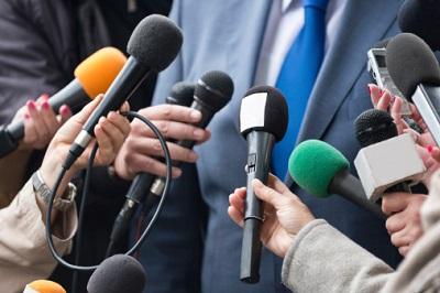 Journalisten halten Mikrofone bei einem Interview