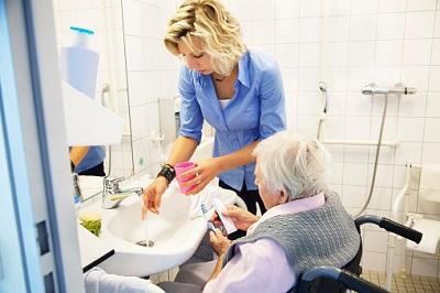 Pflegerin hilft Seniorin beim Zähneputzen im Bad.