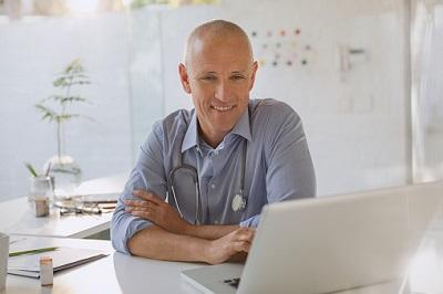 Arzt sitzt im Behandlungszimmer vor dem Laptop